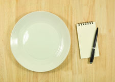 Empty dish and recipe on wood table Stock Image