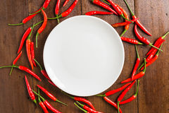 Empty dish, red Chili peppers on wooden background Stock Photo
