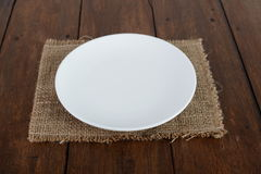 Empty Dish On The Table Background. Empty plate, old fork and knife on wooden background Stock Photos