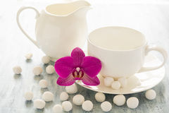 Empty dishes with orhid flower and white candies Royalty Free Stock Images