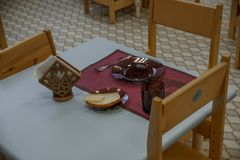 Empty dishes set for breakfast in kindergarden. Kindergarten indoor view. Chairs and tables. Furniture. stock image