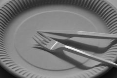 Empty disposable paper plate with plastic fork and knife. stock photo