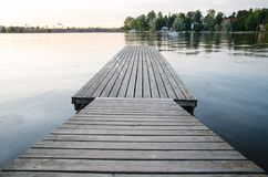 Empty dock in the evening sunset. With view on coast Royalty Free Stock Photos