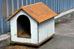 An empty doghouse of plywood near an iron fence. A doghouse with hay from a plywood near a metal fence Stock Images