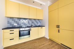 Empty domestic kitchen in yellow color. New apartment, empty with domestic kitchen interior design royalty free stock photo