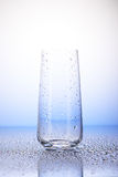 Empty drinking glass in drops of water Royalty Free Stock Photo