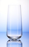Empty drinking glass on white and blue background Stock Photos
