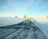 Empty drive cleared of snow. High snow banks by side of road leading up a hill stock photo