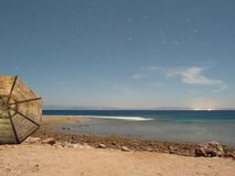 Empty embankment with straw umbrellas in Dahab at night in the moonlight under a starry sky stock images