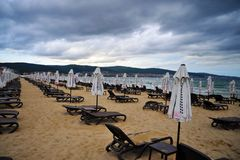 Empty empty beach with folded beach umbrellas stock photography