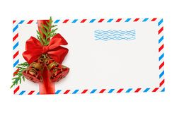 Empty envelope with red and blue borders and stamp tied with ribbon bow and Christmas decorations