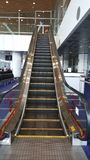 Empty Escalator at an airport conveyance. Front view of a escalator at the airport with stairs going up direction stock photo