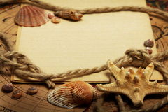 Empty exercise book, seashells and rope. Empty sheet of exercise book, seashells, rope, lying on the maps Stock Image