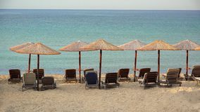 Empty exotic beach with straw umbrellas and blue waters. UHD 4K stock footage