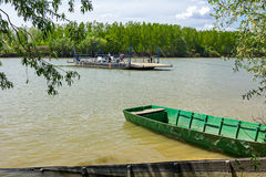 Empty ferry boat is crossing the river, fishing boats are beache Royalty Free Stock Photos