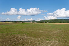 Empty Field and Cloudscape. Field, prepared for the winter with farms in the distance and cloudscape above Stock Photo