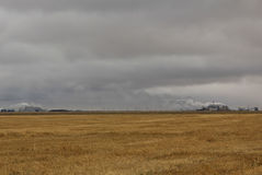 Empty field and refinery. Empty farm field on the prairies with a refinery in the distance Stock Image
