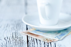 Empty finished white coffee cup and paid cash by euro money on t Royalty Free Stock Photos