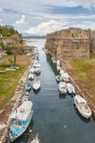 Empty fishing boats in canal under fortress entrance Stock Photos