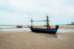 Empty fishing boats. Fishing boats are empty. Parking on the white beach on monsoon day Royalty Free Stock Photo