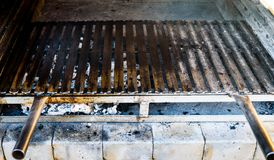 Empty flat barbecue BBQ grill grid in fireplace with charcoal. Big restaurant homemade barbecue fireplace grill with flat metal grid stock image