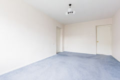 Empty Flat. Interior photo of the empty living room with white walls and gray carpet Royalty Free Stock Photo