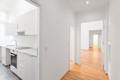 Empty flat, white kitchen and wooden floor Royalty Free Stock Image