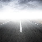 Empty foggy rural asphalt highway perspective. With white line royalty free stock photography
