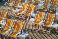 Empty folding beach chairs on a wooden deck Royalty Free Stock Images