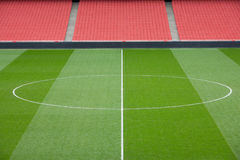 Empty football stadium. Centre circle of a football pitch and bright red seating inside an empty football stadium Royalty Free Stock Images