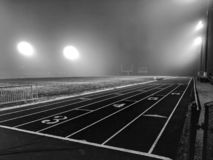 Empty football stadium field at night. Track Lane details pop under bright lights at an empty sports arena stock photography