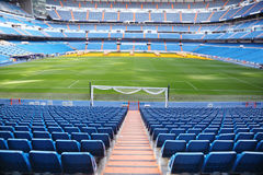 Empty football stadium with seats, rolled gates and lawn. Empty football stadium with blue seats, rolled gates and green lawn stock images