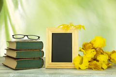 Empty frame with a bouquet of yellow flowers and a pair of glass stock images