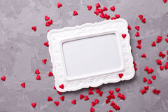 Empty frame and many little  decorative red hearts on textured g Stock Image