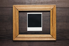 Empty frame and old photo on wooden background Stock Image