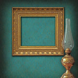 Empty frame on vintage wallpaper and brass oil lam. Empty golden ancient frame on a damask vintage wallpaper with a brass oil lamp Stock Photos