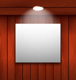 Empty frame on wooden wall lamp illuminated Royalty Free Stock Images