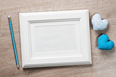Empty frame for your photo. White photo frame small red hearts and pencil on wooden table Stock Images