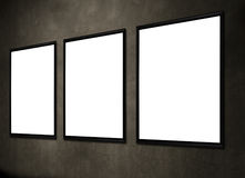 Empty frames. Three white empty frames hanging on a dark wall Royalty Free Stock Photo