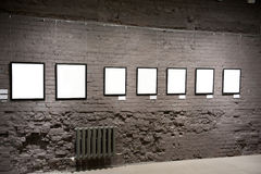 Empty frames on the brick wall Stock Images