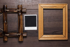 Empty frames and old photo on wooden table Royalty Free Stock Photos