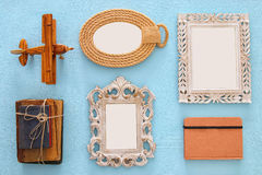 Empty frames ready for mockup, old books and airplane toy. Top view image of empty vintage frames ready for mockup, old books and airplane toy over wooden aqua Stock Photos