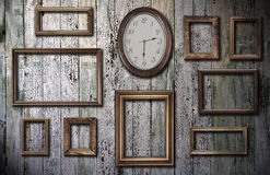 Empty frames and watch on wooden wall Stock Photos