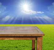 Empty free space top wood table on green grass field against sun. Beam on blue sky use for multipurpose background ,backdrop Royalty Free Stock Photography
