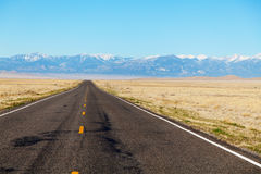 Empty freeway approaching mountains range Royalty Free Stock Images