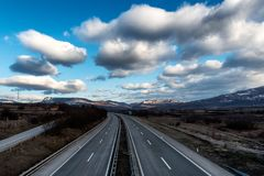 Empty freeway or motorway with beautiful dramatic sky. Empty freeway or motorway with mountains in the background and with beautiful dramatic sky royalty free stock photo