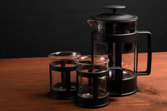 Empty french press with two cups on the wooden table on black background. Empty french press with two cups on the wooden table Royalty Free Stock Photo