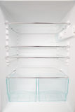 Empty Fridge. A clean and empty refrigerator with white walls and glass shelves Stock Photo