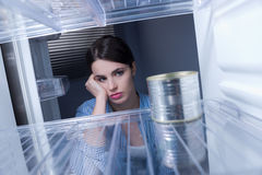 Empty fridge. Young sad woman looking at one tin in her empty fridge Royalty Free Stock Photo