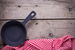 Empty frying pan on aged wooden background. Royalty Free Stock Photo
